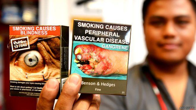 Vendedor de cigarrillos en Australia mostrando dos paquetes con imágenes gráficas