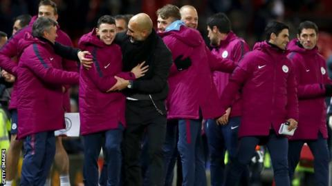 Manchester City players and staff celebrate their derby win at Old Trafford