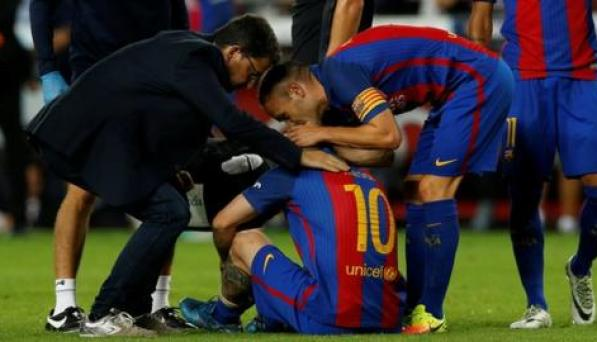 Lionel Messi (number 10) sits on the pitch injured