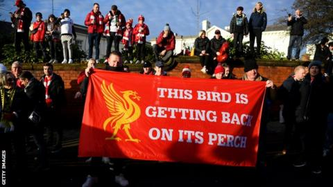 sport Liverpool fans with a flag saying 'The bird is getting back on its perch'
