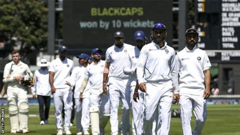Virat Kohli leads a dejected India side off the field after their defeat by New Zealand