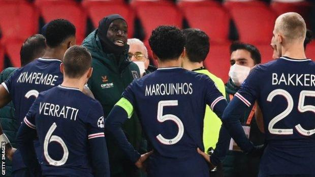 Istanbul forward Demba Ba speaks to the match officials and PSG players