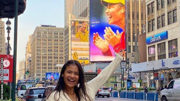 Emma Raducanu smiles and points at a billboard with her face on