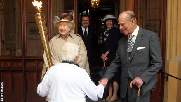 Prince Phillip and the Queen welcome the Olympic torch to Windsor Castle in 2012
