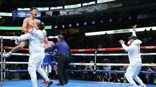 Ryan Garcia is lifted by one of his team after beating Luke Campbell