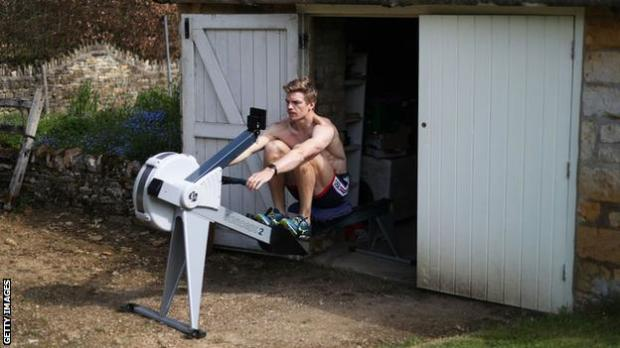 Tom George on a rowing machine outside his parents' garage