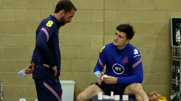 Harry Maguire speaks with England boss Gareth Southgate