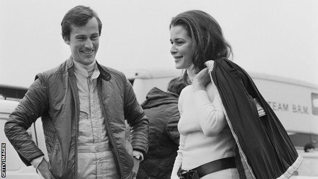 Formula 1 driver Mike Beuttler (left) talks to his companion Anne Ries de Loen (right) stood beside a car at Brands Hatch