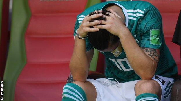 Mesut Ozil holds his head in his hands