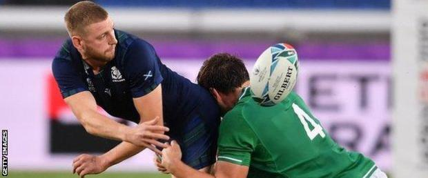 Finn Russell off-loads for Scotland against Ireland