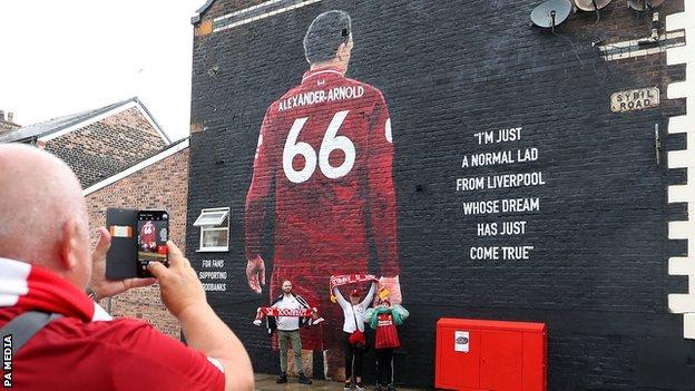 Liverpool fans have their picture taken in front of the Trent Alexander-Arnold mural