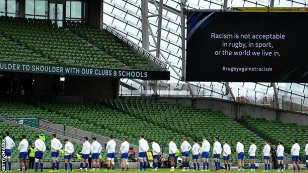 """Rugby players stood in a line with the words """"Racism is not acceptable in rugby, in sport, or the world we live in"""" on the big screen"""