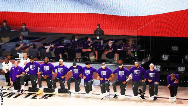 Lakers players kneel during the national anthem while wearing t-shirts emblazoned with 'vote'
