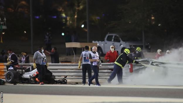 Marshals attend to Romain Grosjean's car