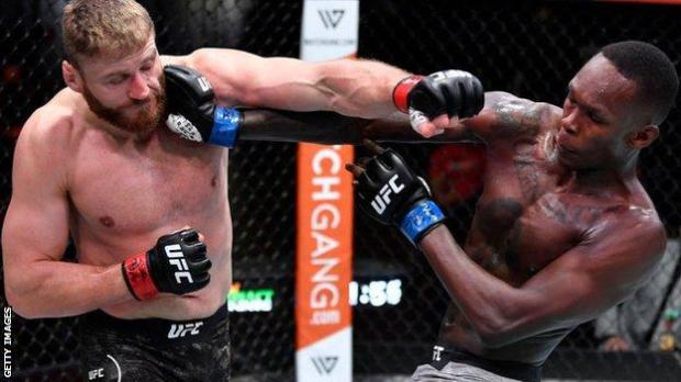 Jan Blachowicz of Poland (left) punches Israel Adesanya of Nigeria in their UFC light heavyweight championship fight during the UFC 259 event in Las Vegas
