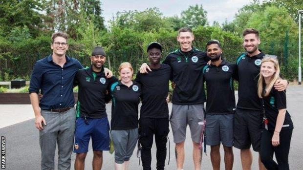 Bukayo Saka (fourth from left) with staff from Greenford High School, including PE teacher Mark Harvey (fourth from right)