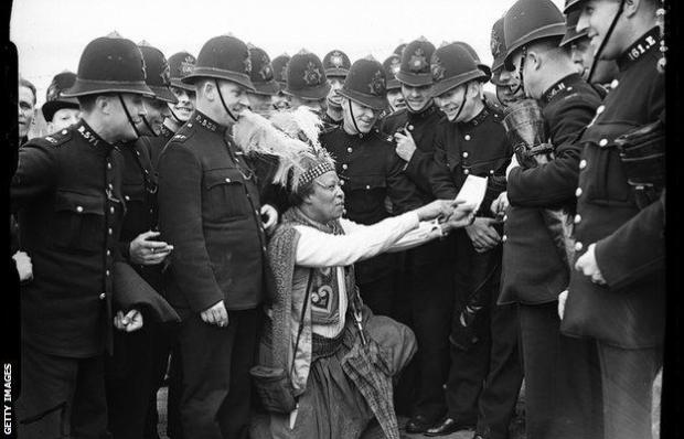Monolulu pictured revealing tips to a large group of police officers at Epsom racecourse, 1938