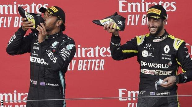 Lewis Hamilton and Daniel Ricciardo do a shoey on the podium