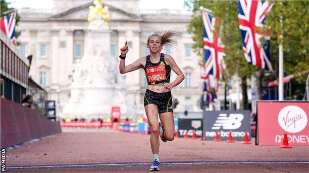 Charlotte Purdue crosses the finish line of the London Marathon with Buckingham Palace in the background