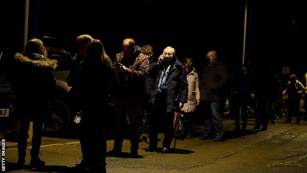 Fans form socially distant queues as they wait to enter Adams Park