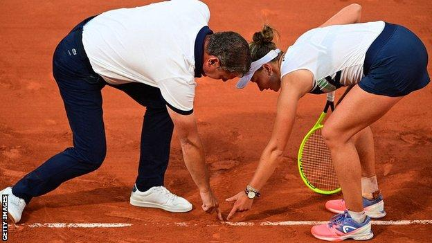 Barbora Krejcikova and umpire Pierre Bacchi check the line