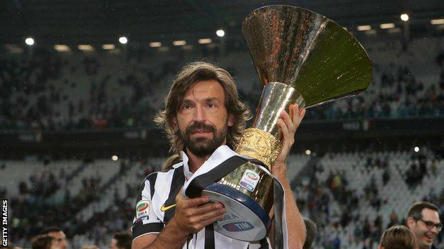 Andrea Pirlo holds up the Serie A trophy while a player for Juventus