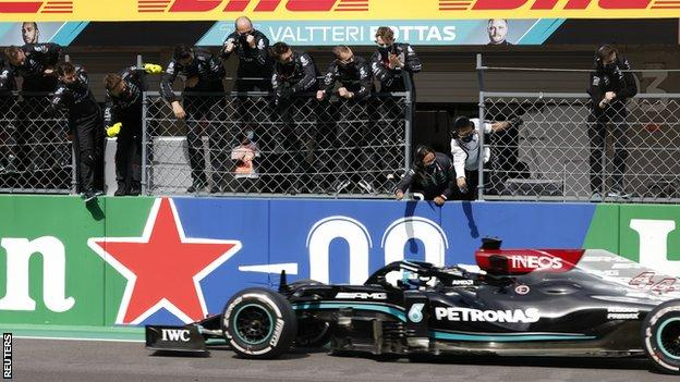 Mercedes crew celebrate as Lewis Hamilton drives past