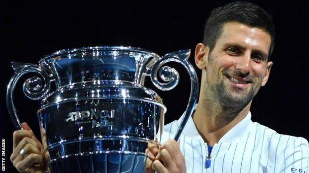 Novak Djokovic collects the trophy for finishing 2020 as the world's top men's player