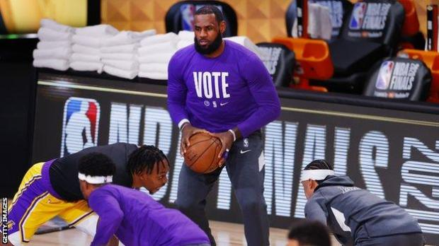 LeBron James warming up wearing a T-shirt with the word 'vote' on the front