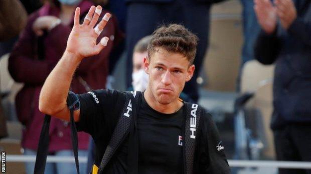 Diego Schwartzman waves goodbye to the Roland Garros crowd after losing to Rafael Nadal