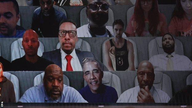Big screen showing 'virtual' fans including Barack Obama