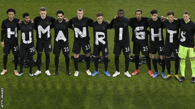 Germany's starting side link arms while wearing black t-shirts, each with a white letter on them, spelling out 'Human rights' before their 2022 World Cup qualifier against Iceland to show support for migrant workers building stadiums in Qatar