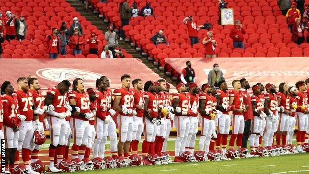 Kansas City Chiefs players link arms in a 'moment of unity' as the reduced crowd allowed into Arrowhead Stadium watch on