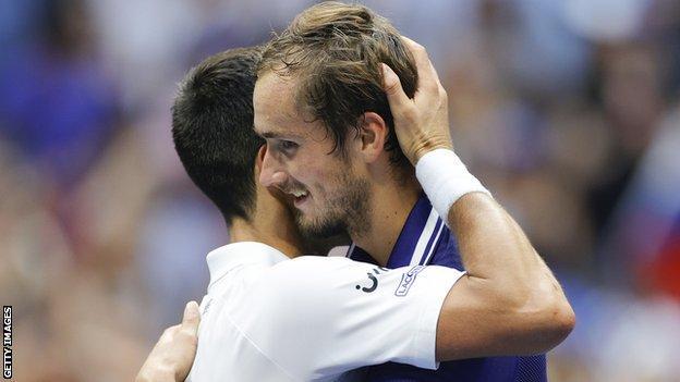 Daniil Medvedev hugs Novak Djokovic