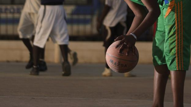 A woman holds a basketball in her hands