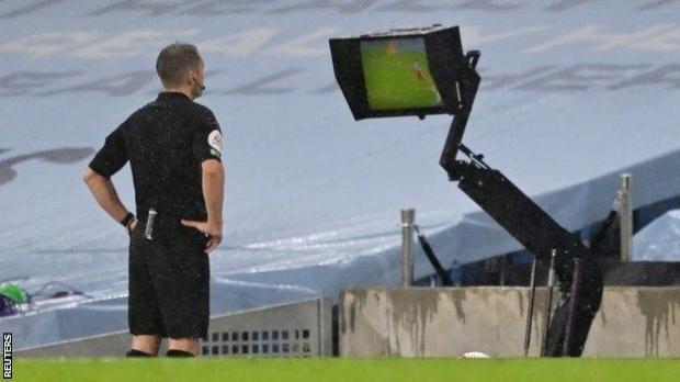 Referee Craig Pawson looks at VAR monitor