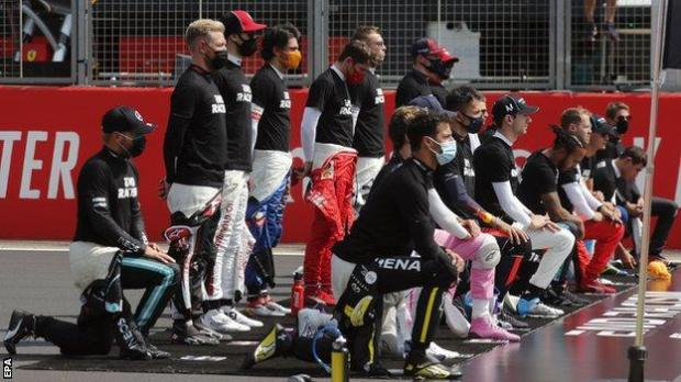 Drivers take the knee or stand