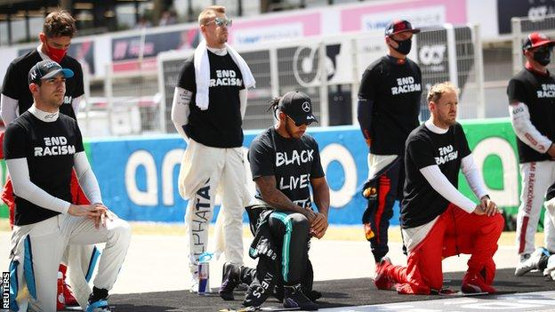 Drivers kneel or stand during the anti-racism protest