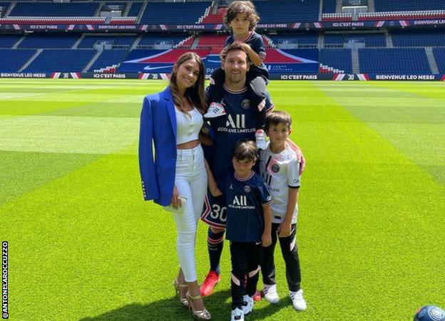 Lionel Messi and family pose for a photo on the Parc des Princes pitch
