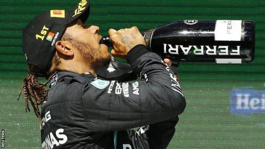 Lewis Hamilton drinks champagne on the podium
