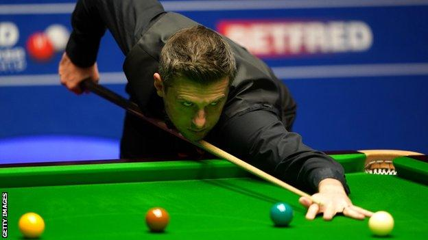 Selby edges towards final as match paused