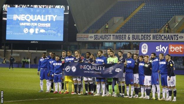 Millwall and QPR players holding an anti-racism banner before their game on 8 December 2020