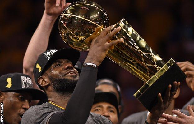 LeBron James holding aloft the NBA Championship trophy in 2016