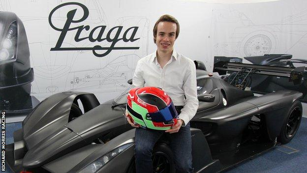 Britcar Endurance Championship driver and racing pride co-founder Richard Morris holds up his helmet while leaning against a car