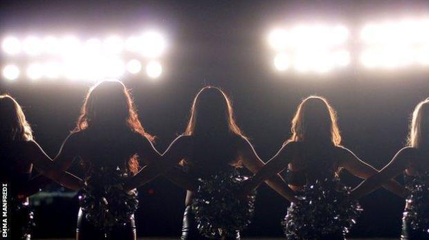 Cheerleaders in silhouette.