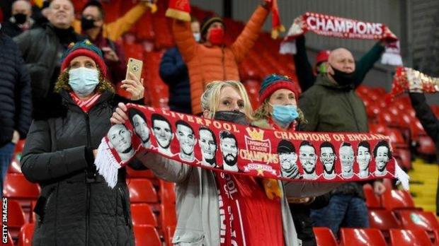 Liverpool fans hold their scarves up before kick off against Wolves