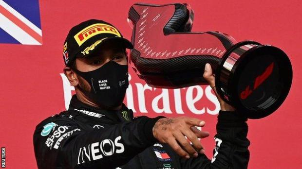 Lewis Hamilton holds up the winner's trophy