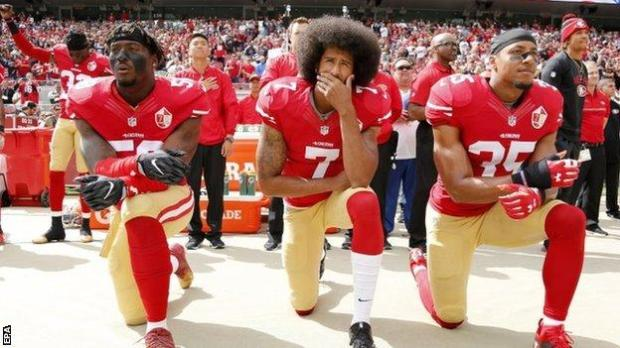 Eli Harold, Colin Kaepernick and Eric Reid take a knee as protest against police brutality and racial injustice