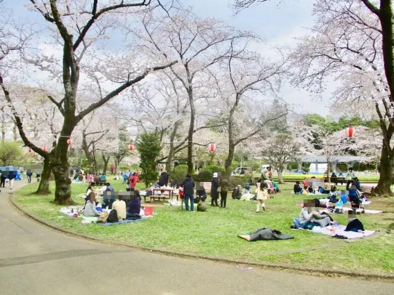 芝生広場でレジャーシートでくつろぐ人々