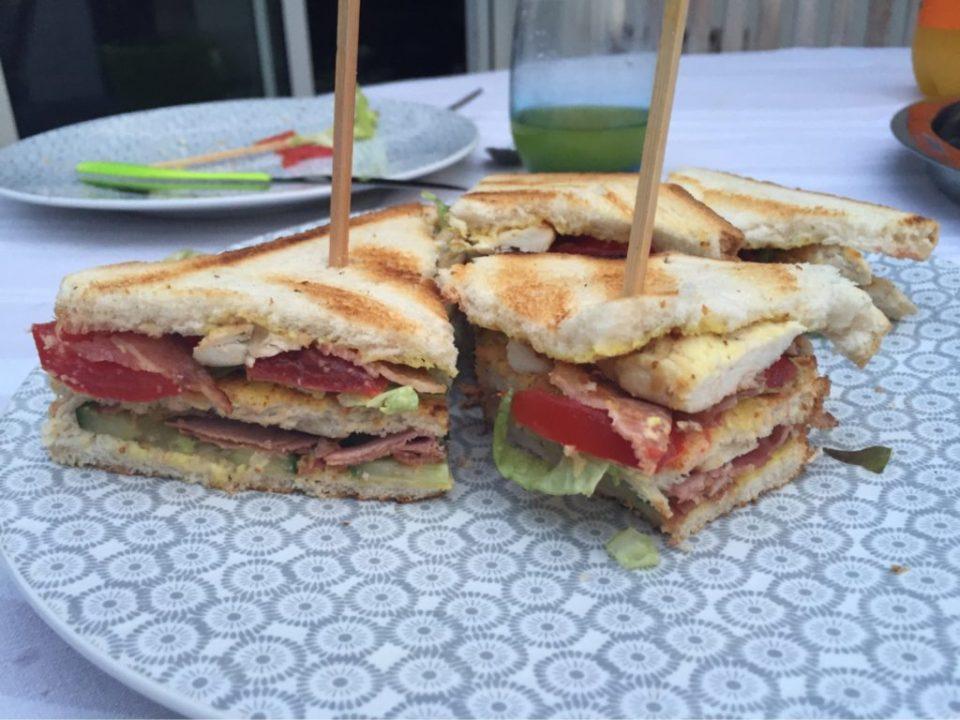 Club sandwich composé de pain de mie toast, avec moutarde ou mayonnaise et des couches successives de bacon grillé concombres, tomates, salade et poulet grillé.